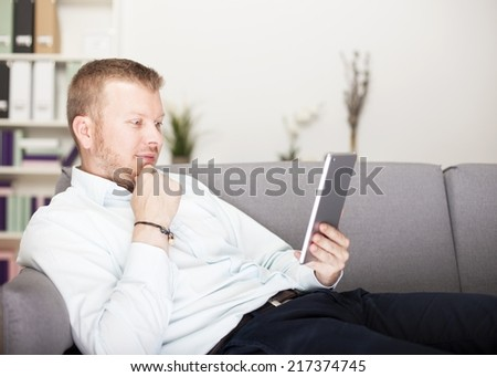 Thoughtful man reading his tablet computer as he relaxes on a couch with his hand to his chin and a pensive expression - stock photo