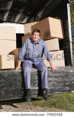Thoughtful man sitting in the truck with pile of boxes behind him - stock photo