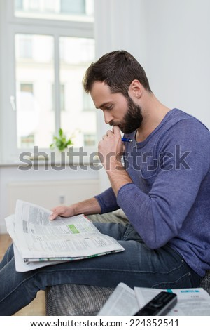 Thoughtful man sitting reading a newspaper at home with his hand to his chin as he concentrates on the news