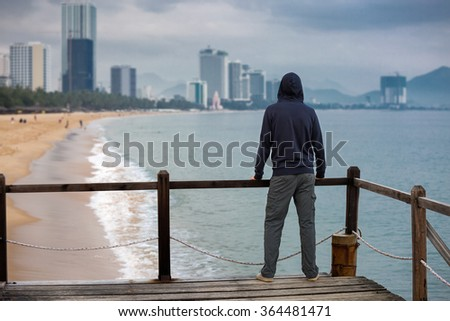 Thoughtful man standing on sea pier looking at city skyline, shot from behind. Emigration and new beginning concept - stock photo