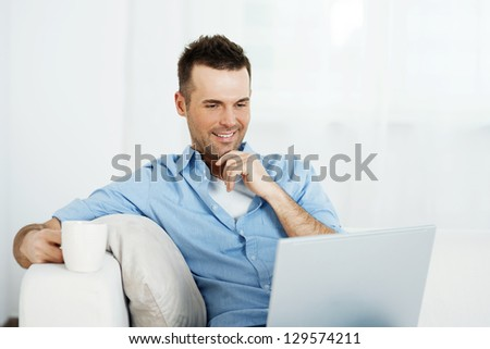 Thoughtful man with laptop and cup of coffee