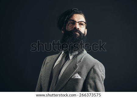 Thoughtful Man with Long Facial Hair Wearing Checkered Formal Wear with Glasses, Looking to the Right of the Frame Seriously on a Black Background. - stock photo