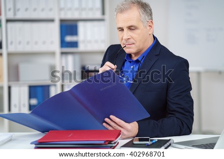 Thoughtful manager reading through a report or CV in a blue folder with a look of concentration as he sits at his desk in the office