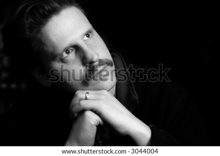 Thoughtful, married man with folded hands (black and white, shallow focus)