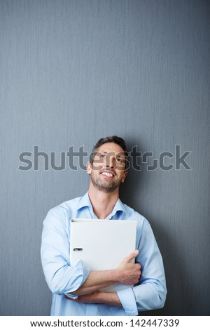 Thoughtful mature businessman holding binder while looking up against blue wall - stock photo