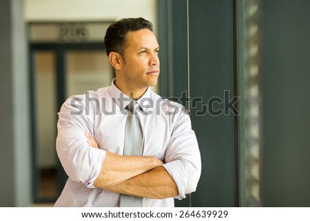 thoughtful mature businessman looking outside office window - stock photo