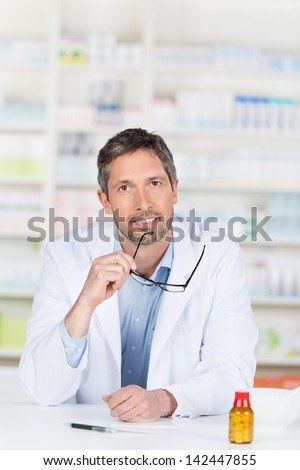 Thoughtful mature male pharmacist holding glasses at pharmacy counter - stock photo