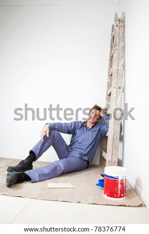 Thoughtful mature man sitting on floor with paint bucket beside - stock photo