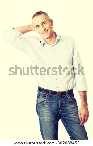 Thoughtful mature man touching his head. - stock photo