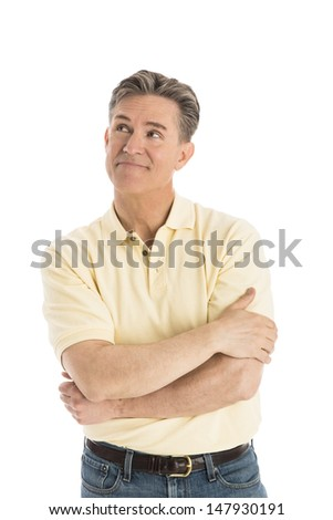 Thoughtful mature man with arms crossed looking away while standing isolated over white background