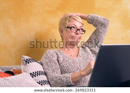 Thoughtful Middle Age Blond Woman Sitting at Sofa While Holding her Head and Looking Up with Laptop Computer.