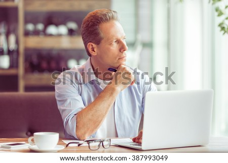 Thoughtful middle aged businessman in casual clothes is using a laptop while working at the restaurant - stock photo