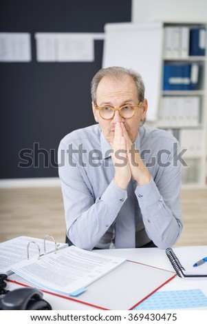 Thoughtful middle-aged businessman wearing eyeglasses sitting at his desk seeking a solution to a problem with a contemplative expression - stock photo