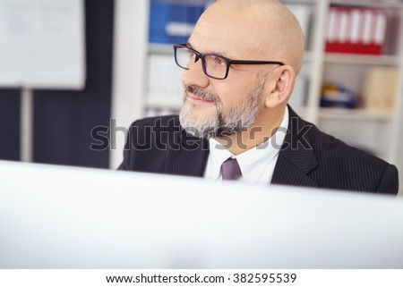 Thoughtful middle-aged businessman wearing glasses sitting behind his computer monitor staring off into the distance - stock photo