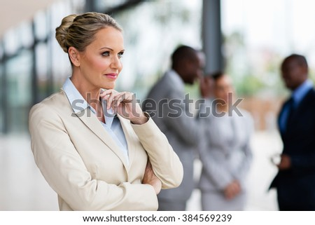 thoughtful middle aged businesswoman in modern office