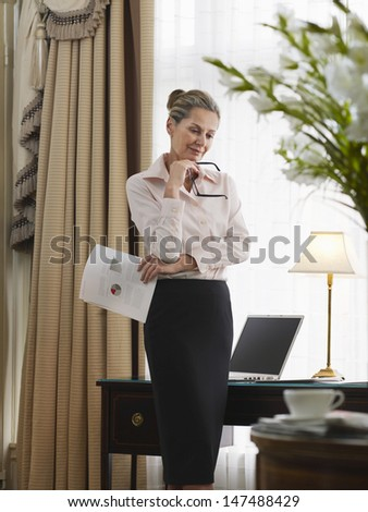 Thoughtful middle aged businesswoman with document in home office - stock photo