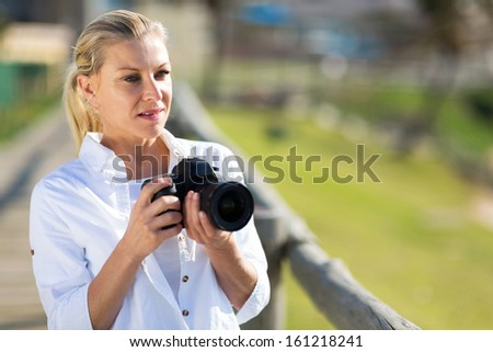 thoughtful middle aged female photographer holding camera outdoors