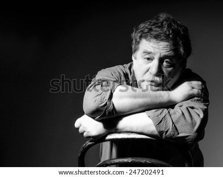 Thoughtful middle-aged man with a mustache in a plaid shirt rests on the back of deployed upside down, look at the camera. Old style photo. - stock photo