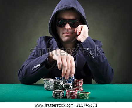 Thoughtful poker player on black background - stock photo