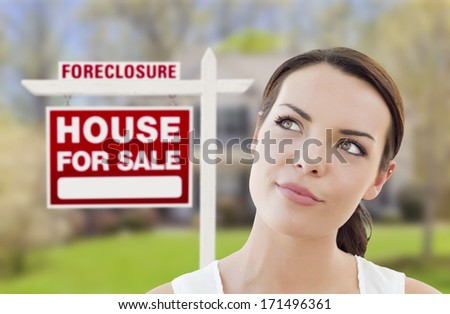 Thoughtful Pretty Mixed Race Woman In Front of Home and Foreclosure House For Sale Real Estate Sign Looking Up and to the Side. - stock photo