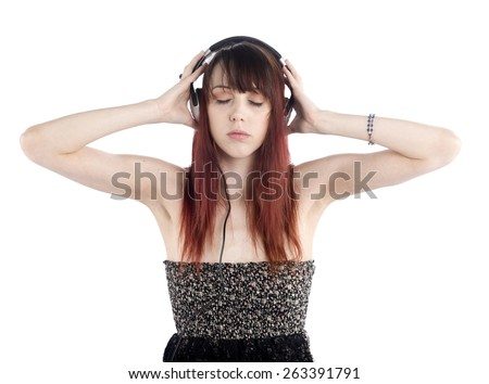 Thoughtful Pretty Woman Enjoying the Music While Holding her Headphone on her Ears. Isolated on White Background. - stock photo