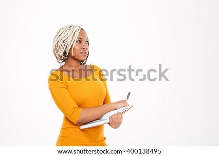 Thoughtful pretty young african american woman writing in notebook and thinking over white background - stock photo