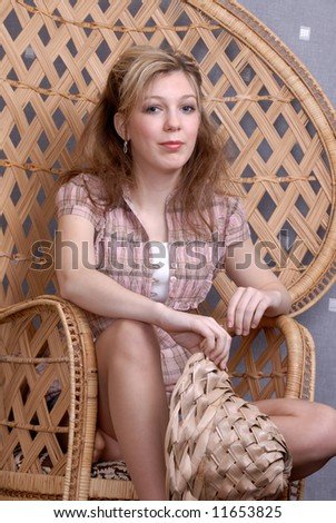 thoughtful pretty young blonde  teenage girl on wickerwork seat holding straw hat