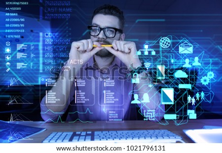Thoughtful programmer. Concentrated experienced smart programmer sitting in front of a modern transparent screen and biting his pencil while thinking about the last cyber attack