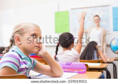 Thoughtful pupil sitting at her desk at the elementary school - stock photo