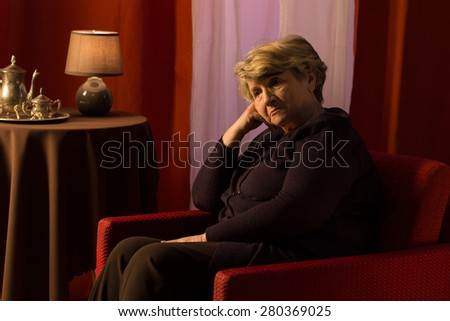Thoughtful sad woman sitting in vintage style room - stock photo