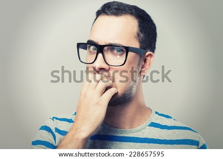 Thoughtful sceptical young man  - stock photo