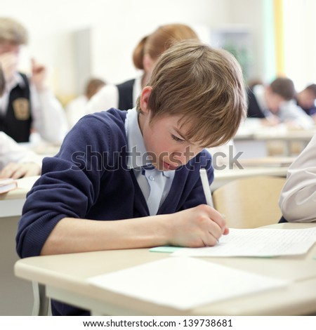 thoughtful school boy struggling to finish test in class. - stock photo