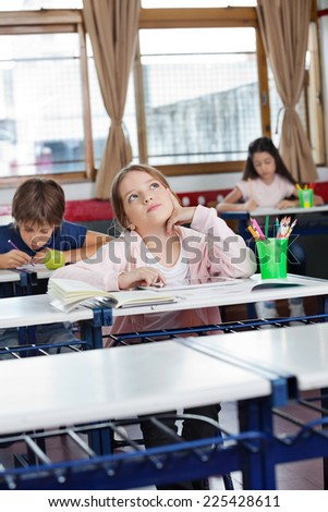 Thoughtful schoolgirl looking up with digital tablet at desk while friends studying in background - stock photo