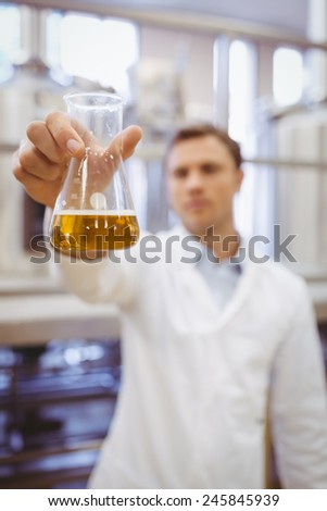 Thoughtful scientist holding a beaker in the factory - stock photo