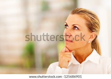 thoughtful senior businesswoman looking up - stock photo
