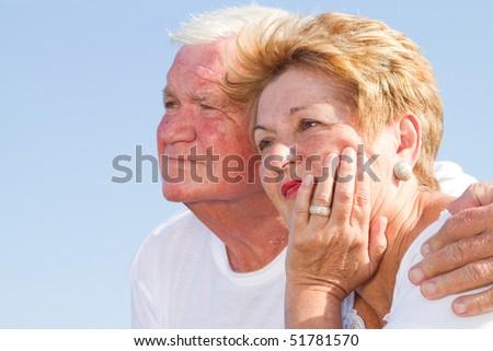 thoughtful senior couple hugging - stock photo