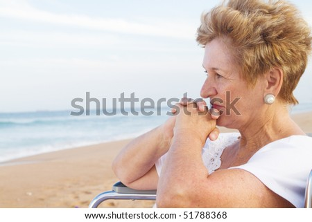 thoughtful senior disabled woman sitting on wheelchair on beach - stock photo