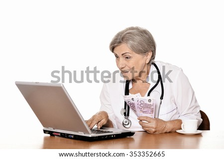 Thoughtful senior doctor sitting at table with laptop