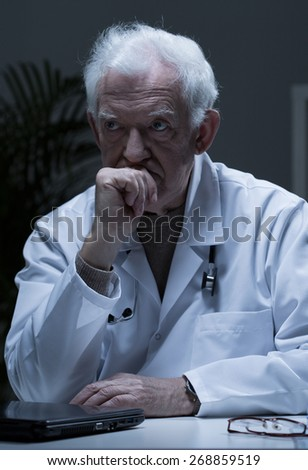Thoughtful senior doctor sitting at the desk - stock photo