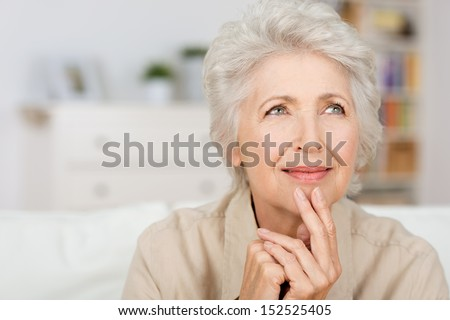Thoughtful senior lady sitting at home with her fingers to her chin reminiscing and recalling fond memories, close up portrait - stock photo