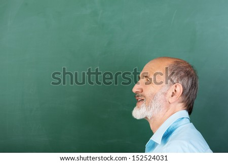 Thoughtful senior male teacher or businessman standing thinking in front of a blank green chalkboard with copyspace, head and shoulders profile view - stock photo