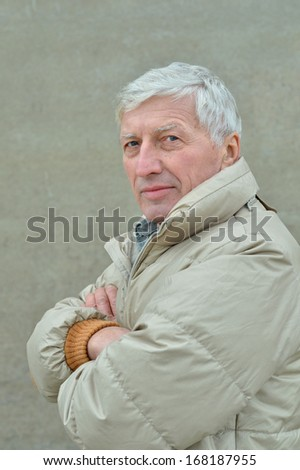 Thoughtful senior man at grey outdoor background