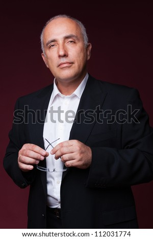 thoughtful senior man holding glasses and looking at camera