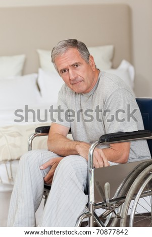Thoughtful senior man in his wheelchair  at home - stock photo