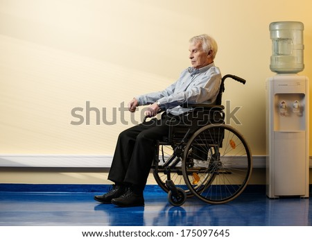 Thoughtful senior man in wheelchair in nursing home  - stock photo