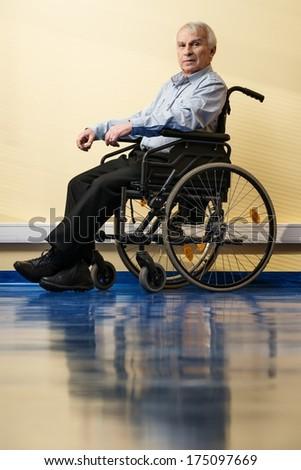 Thoughtful senior man in wheelchair in nursing home  - stock photo