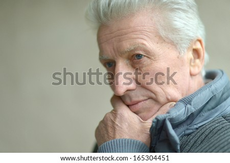 Thoughtful senior man portrait. standing against wall