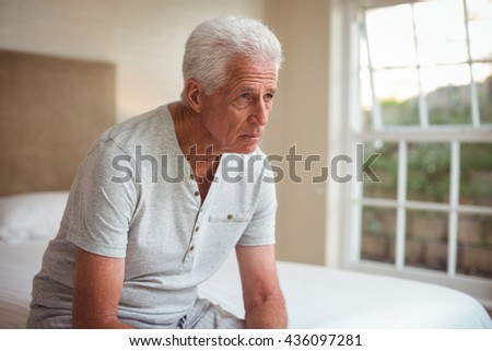 Thoughtful senior man sitting on bed in room - stock photo