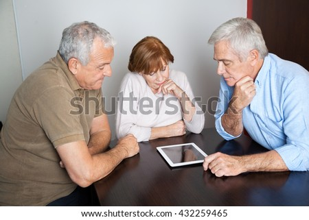 Thoughtful Senior People Using Digital Tablet In Computer Class - stock photo