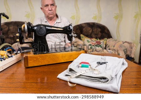 Thoughtful Senior Tailor Man Sitting at the Table with Sewing Tools and a Cloth Inside his House. - stock photo